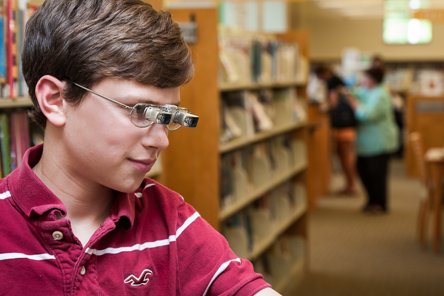 Young boy using Ocutech SightScope bioptics to read books in a library