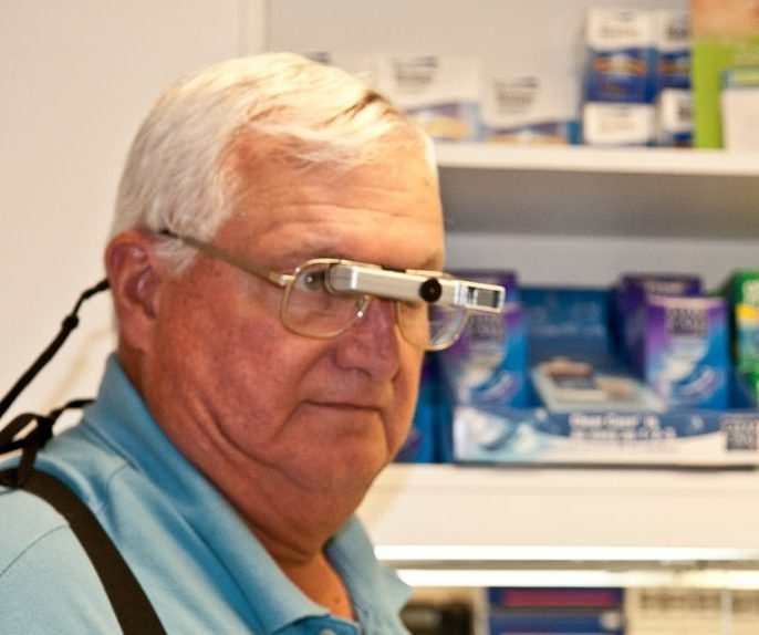 Senior citizen using Ocutech Sport bioptics to view items in a pharmacy