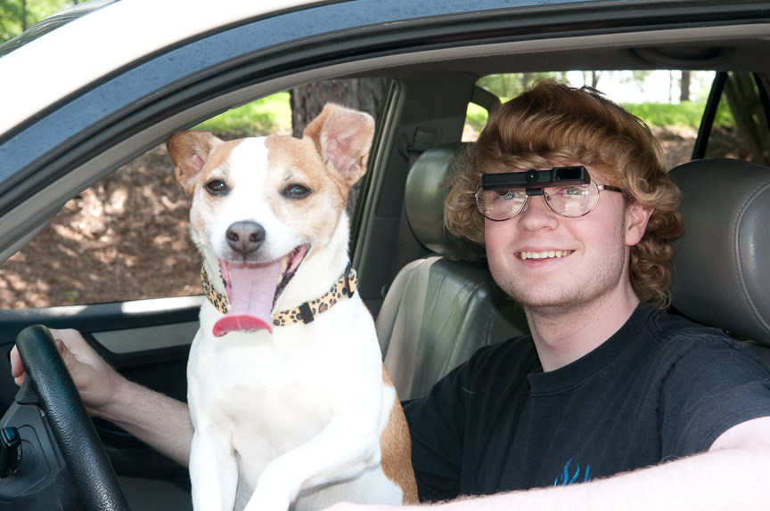 Teenage boy driving while wearing bioptics and dog is in car