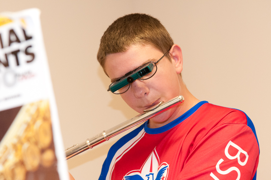 young boy playing flute and reading music