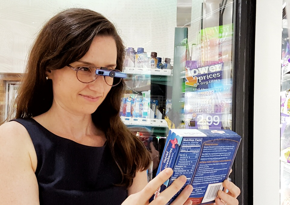 Young adult female using Ocutech Explorer bioptics to read items in a grocery store