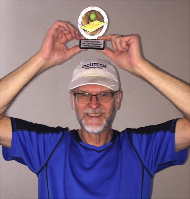 Low Vision Specialist wearing Ocutech hat and holding tennis trophy above head